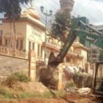 An-excavator-demolishing-a-section-of-Visa-Oshwal-Center