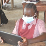 Pupil using tablet in class for digital learning